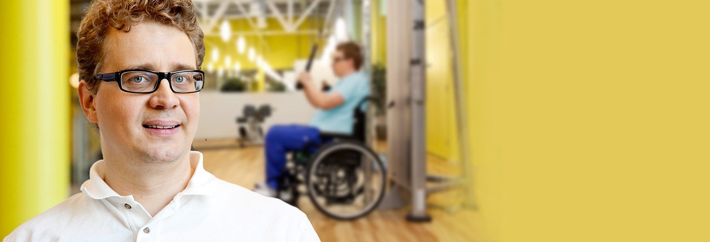 A man is looking into the camera, and in the background there is a person in a wheelchair